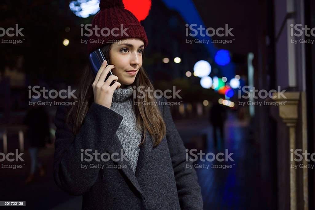 Portrait of young woman using her mobile phone at night. stock photo