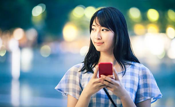 の肖像若い女性電話を使用して通りを夜に - 女性 横顔 日本人 ストックフォトと画像