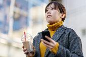 スマートフォンを使い、タピオカミルクティーを持つ若い女性の肖像画