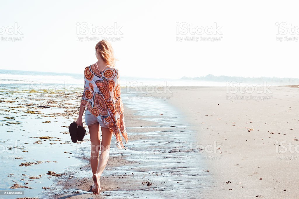 Portrait of young woman walking on the beach stock photo