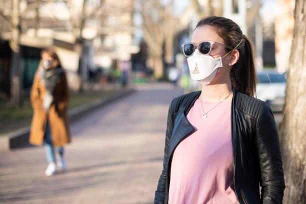 Porträt einer jungen Frau, die während einer Infektion eine Gesichtsmaske auf der Straße trägt – Foto