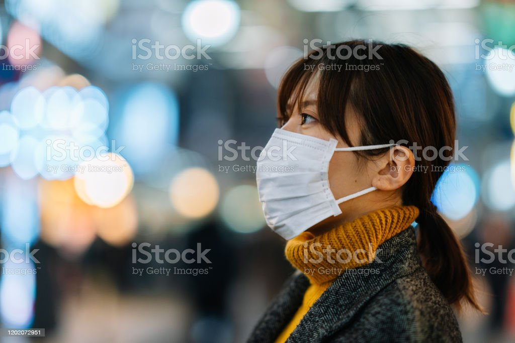Portrait of young woman wearing face mask A portrait of a young woman wile wearing a face mask for protection from cold and flu and viruses. 20-29 Years Stock Photo