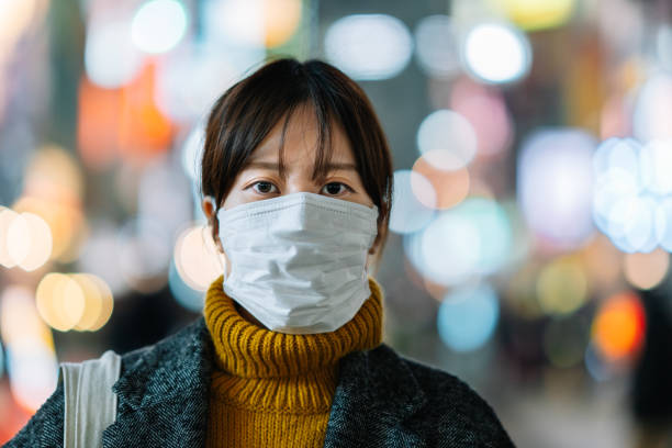 Portrait of young woman wearing face mask A portrait of a young woman wile wearing a face mask for protection from cold and flu and viruses. middle east respiratory syndrome stock pictures, royalty-free photos & images