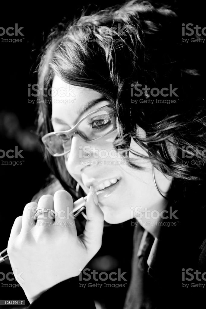 Portrait of Young Woman Wearing Glasses and Holding Pen royalty-free stock photo