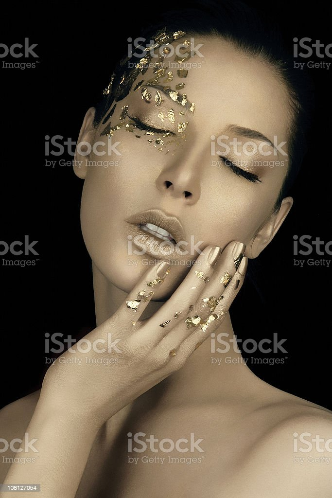 Portrait of Young Woman Wearing Gold Flake Make-up royalty-free stock photo