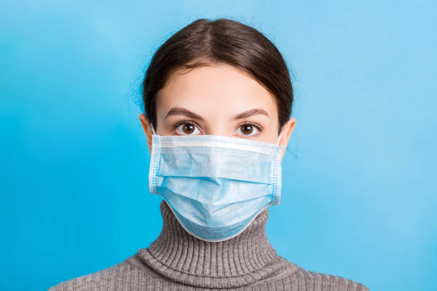 Portrait of young woman wearing medical mask at blue background. Protect your health. Coronavirus concept stock photo