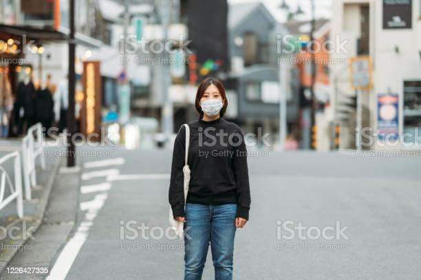 空の通りで保護フェイスマスクを着用した若い女性の肖像画 - 1人のストックフォトや画像を多数ご用意