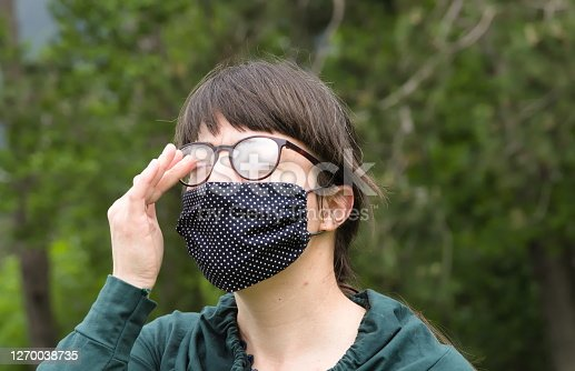 Portrait of Young Woman Wearing Protective Mask and Eyeglasses and Making Face because of Bad Air under Mask