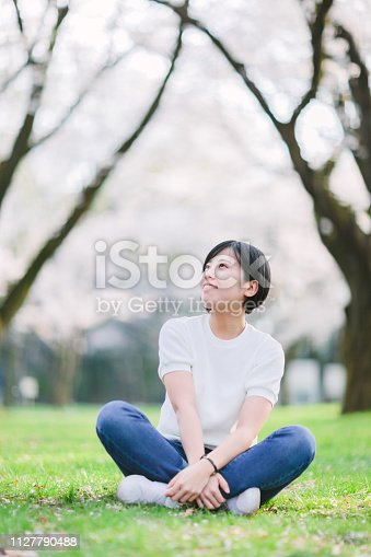 A portrait of a young woman under sakura trees.