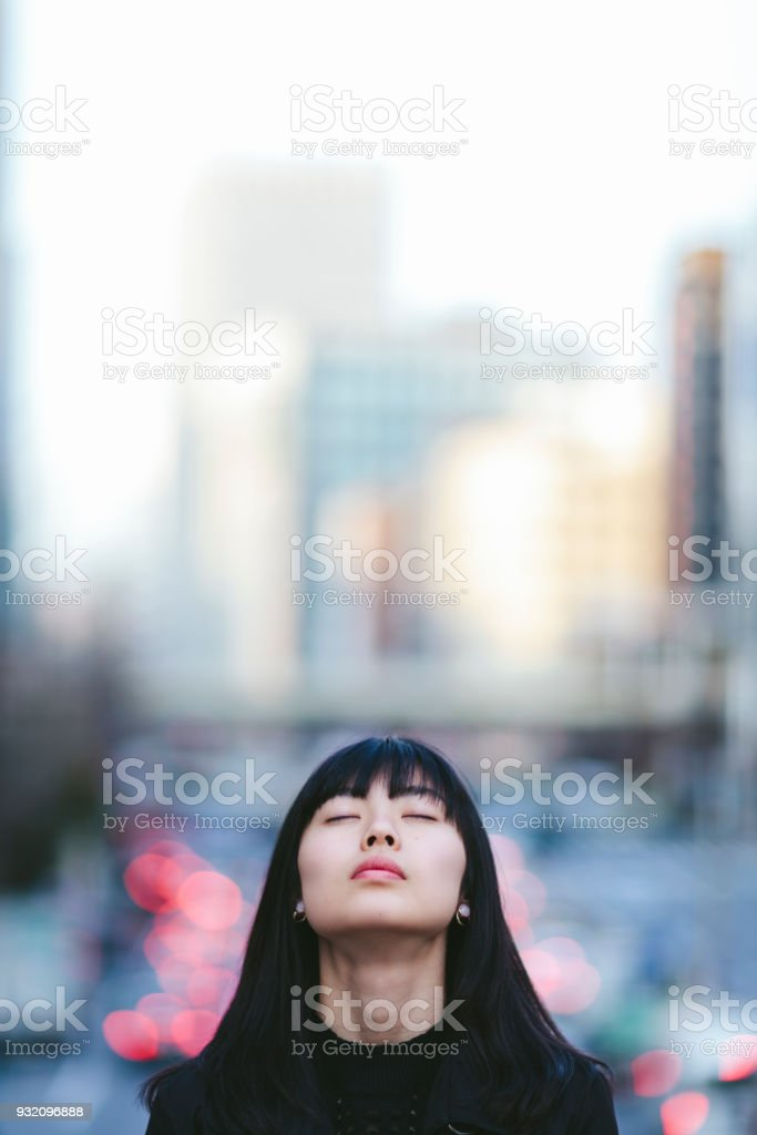 Portrait of young woman whileher eyes are closed in the city A portrait of a young woman while her eyes are closed in the city. 20-29 Years Stock Photo