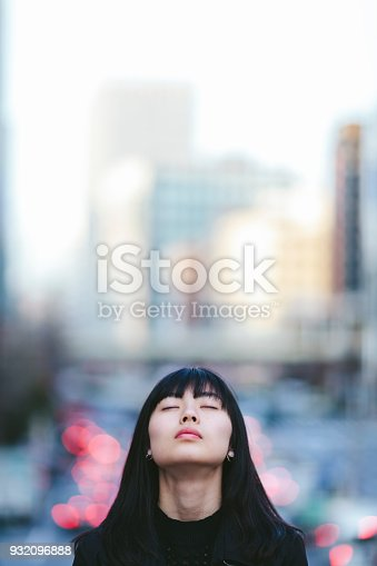 A portrait of a young woman while her eyes are closed in the city.