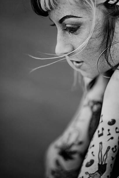porträt der jungen frau mit armen tattoos, schwarz und weiß - musiknoten tattoos stock-fotos und bilder