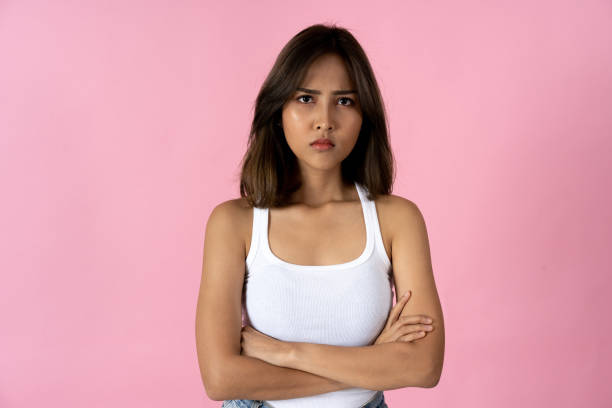 Portrait of young woman with arms folded against pink background stock photo