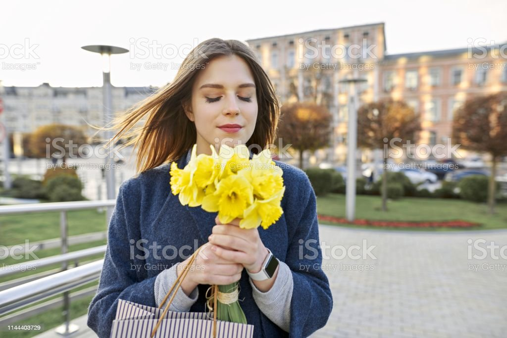 Portrait of young woman with bouquet of yellow spring flowers daffodils. Beautiful girl in city enjoys flowers, eyes closed. royalty-free stock photo