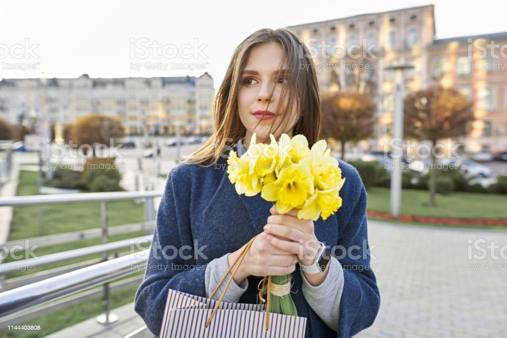 Portrait of young woman with bouquet of yellow spring flowers daffodils. Beautiful girl close up, spring city background royalty-free stock photo