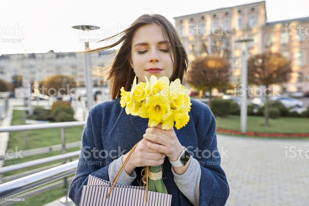 Portrait Of Young Woman With Bouquet Of Yellow Spring