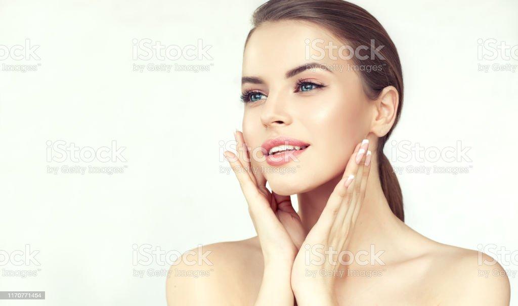 年輕女子的肖像與乾淨的新鮮皮膚和柔軟,精緻的化妝。女人溫柔地撫摸著臉。 - 免版稅一個人圖庫照片