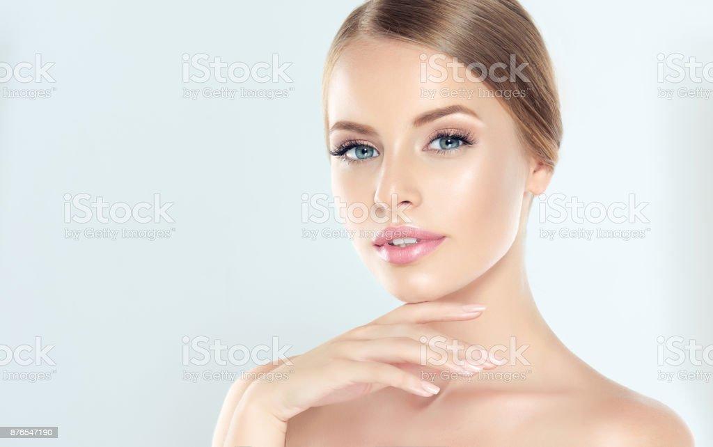 年輕女子的肖像, 清新的皮膚和柔軟, 細膩的彌補。女人溫柔地撫摸著自己的臉。 - 免版稅一個人圖庫照片