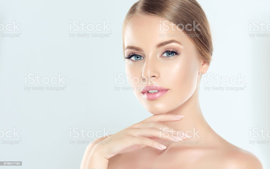 Portrait of young woman with clean fresh skin and soft, delicate make up. Woman  is touching tenderly to own face. stock photo