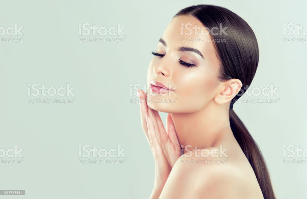 Portrait of young woman with clean fresh skin and soft, delicate make up. Woman  is touching to own face tenderly. - Foto stock royalty-free di Accudire