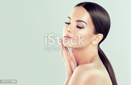 istock Portrait of young woman with clean fresh skin and soft, delicate make up. Woman  is touching to own face tenderly. 917717364