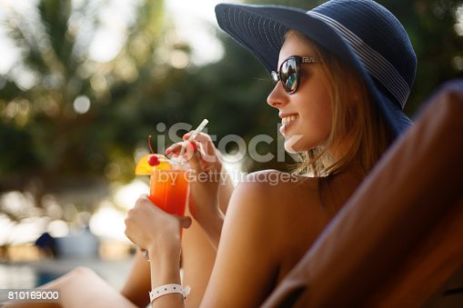 istock Portrait of young woman with cocktail glass chilling in the tropical sun near swimming pool on a deck chair with palm trees behind. Vacation concept 810169000