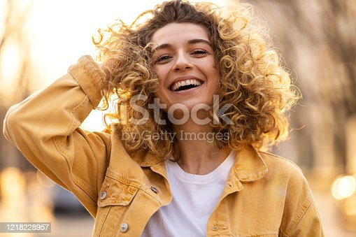 istock Portrait of young woman with curly hair in the city 1218228957
