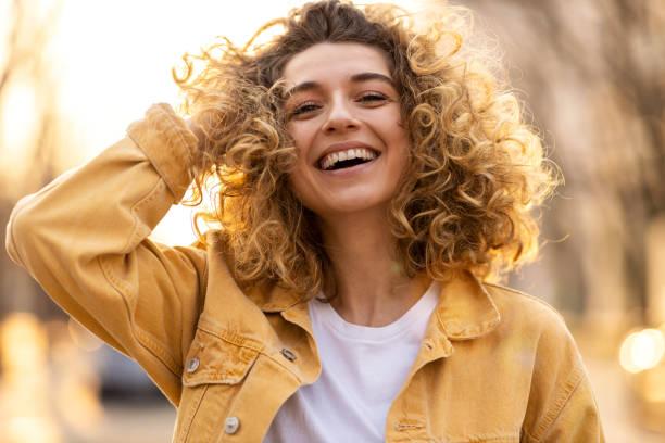 城市中捲髮的年輕女子的肖像 - 幸福 個照片及圖片檔