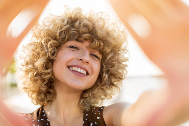 portrait of young woman with curly hair - capelli ricci foto e immagini stock