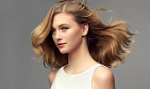Model with dark blonde hair. Frizzy, flying hair is surrounding pretty face of tenderly smiling young woman. Natural gloss and softness of healthy hair. Hair care and hairdressing art.