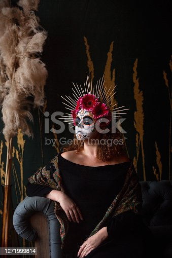 Young women with face painted as fashionable skull for Mexican holiday Day of the Dead.