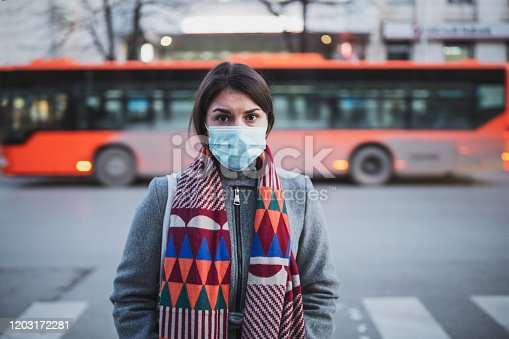 Young woman standing in front of crossroad and looking at camera, she looking sick in front of blurred bus transportation vehicle, looking at camera.