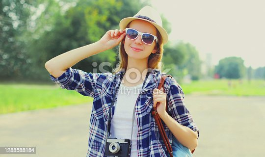 Portrait of young woman with film camera wearing a summer straw hat, shirt outdoors