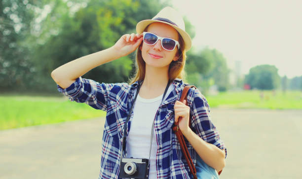 Portrait of young woman with film camera wearing a summer straw hat, shirt outdoors stock photo