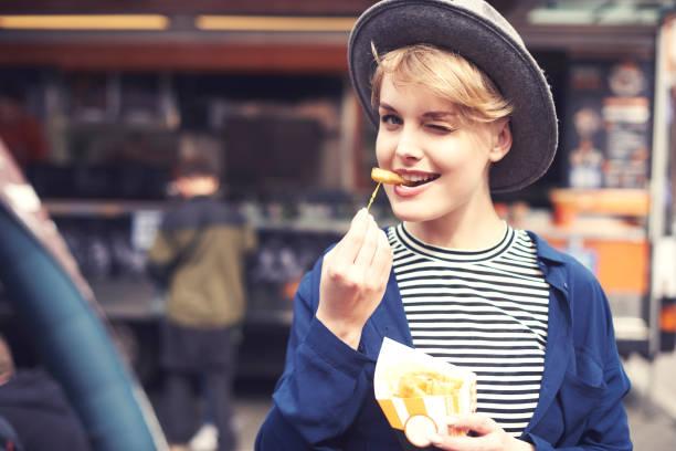 porträt der jungen frau mit pommes augenzwinkernd - streetfood stock-fotos und bilder