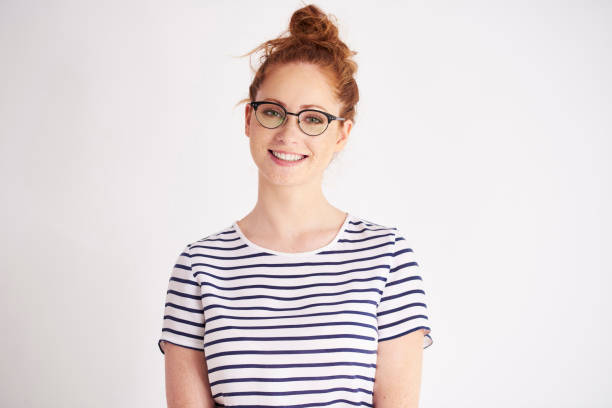 Portrait of young woman with glasses at studio shot stock photo