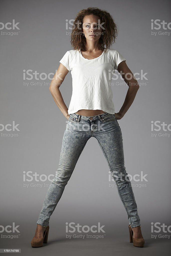 Portrait of young woman with hands on hips,  grey background stock photo