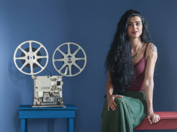 Portrait Of Young Woman With Long Black Hair Posing With Film Projector stock photo
