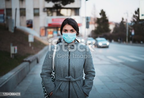 Portrait of young Latino woman with face mask on the street, looking at camera.