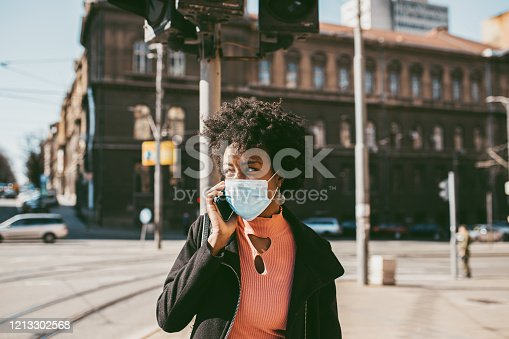 Young Afro American woman standing and using smart phone on city street with protective mask on her face. Virus pandemic and pollution concept.