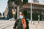 Young Afro American woman standing on city street with protective mask on her face. Virus pandemic and pollution concept.