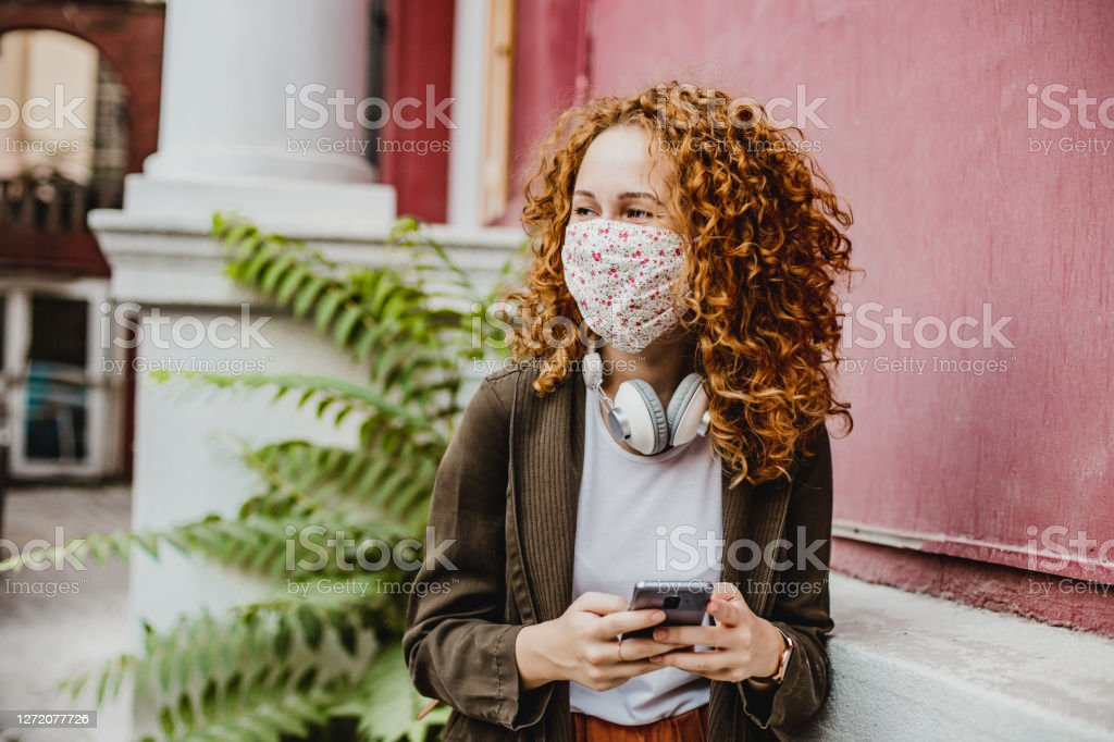 Portrait of young woman with mask using smart phone Portrait of young woman standing next to red wall and smiling 20-29 Years Stock Photo