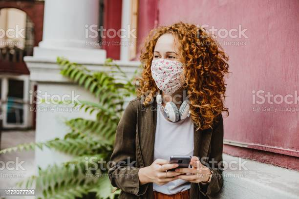 Portrait Of Young Woman With Mask Using Smart Phone Stock Photo - Download Image Now