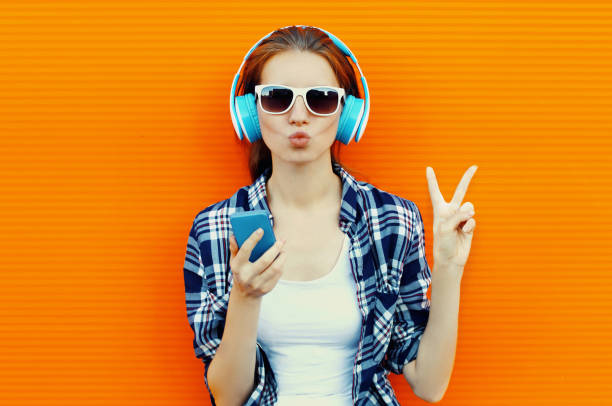Portrait of young woman with phone in wireless headphones listening to music on orange background stock photo