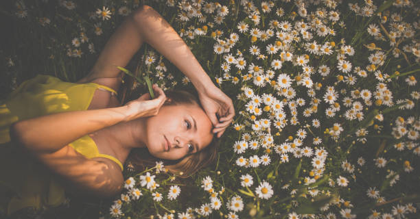 Portrait of young  woman with radiant clean skin lying down amid flowers Portrait of young  woman with radiant clean skin lying down amid flowers on a lovely meadow on a spring/summer day amid stock pictures, royalty-free photos & images