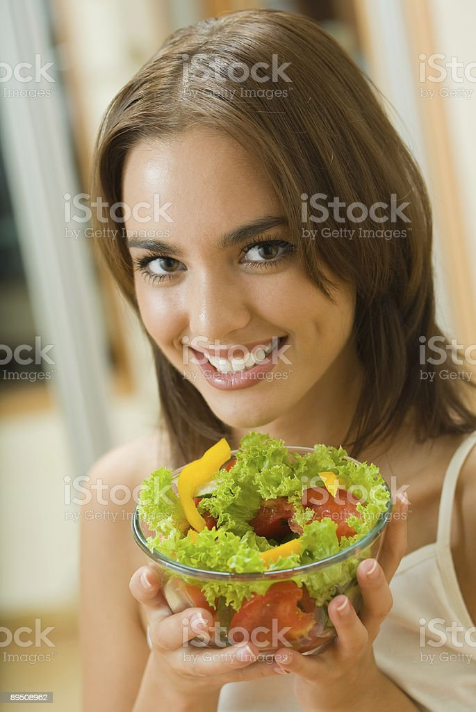 Portrait of young woman with salad at home royalty-free stock photo