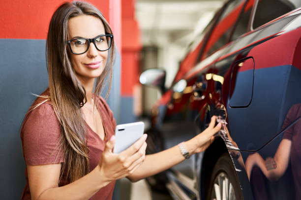 portrait of young woman with scratched car at underground parking lot - dent stock pictures, royalty-free photos & images