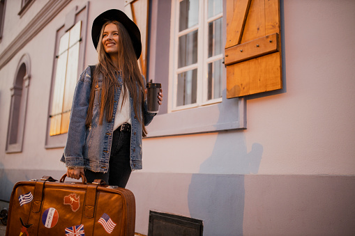 Portrait of young woman with suitcase drinking coffee in new city