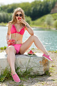 A young woman in sunglasses with melon refreshes. She sits astride in a bikini on a large stone and eats watermelon. Blurred natural background with a water surface. Shooting with Canon EOS 5D Mark II.