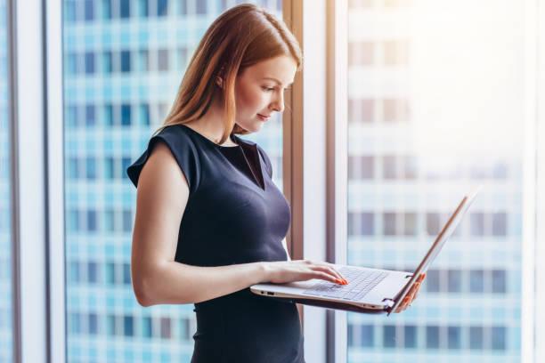 Porträt der jungen Frau, die arbeitet Holding Laptop gegen Panoramafenster mit Blick auf die Stadt – Foto